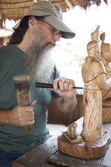 Mixed race man carving wooden statue