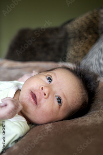 Mixed race newborn baby laying on blanket