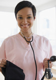 Mixed race doctor holding blood pressure gauge
