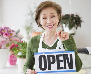 Japanese florist holding open sign