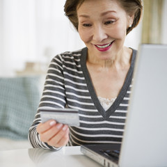 Japanese woman holding credit card using laptop