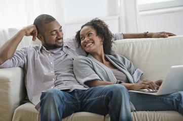 Black couple on sofa using laptop