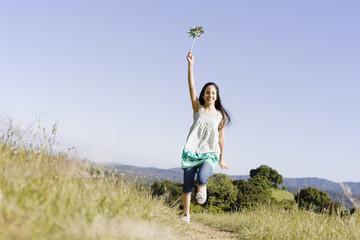 Hispanic girl running with pinwheel