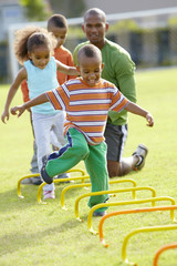 African American boy running across obstacle course