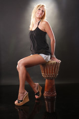 Cute blond sitting on an African drum