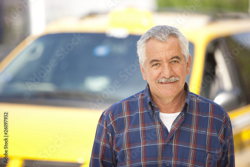 Middle Eastern man posing in front of taxi