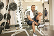 African American man resting in health club on weight-lifting bench