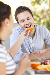 Woman feeding orange to man