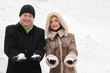 man and girl in warm dress smiling and holding snowballs