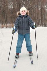 boy in warm sport dress skiing at forest, full body