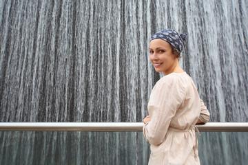 beauty woman in white shirt standing near big fountain