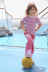 girl with ball standing near football goal on cruise liner