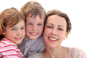 family with mother, daughter and son smiling and looking