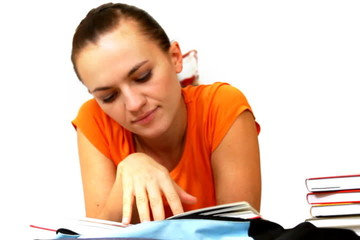 Young student lying and reading book, isolated
