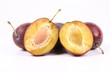 Plums on white background - one cut in half with a pit visible