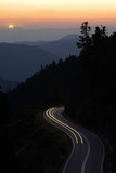car travelling winding road between mountain at sunset poster