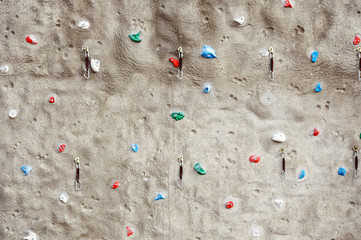 Climbing wall with different colorful holds and carabiner hooks