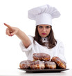 pointing female chef with doughnuts