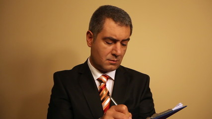 Businessman writing document on clipboard