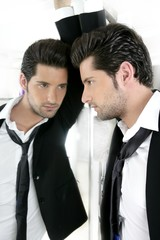 Handsome narcissistic young man looking in a mirror