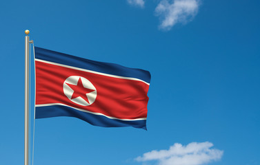 Flag of North Korea waving in the wind in front of blue sky