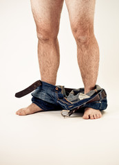 Man's bare legs with pants down