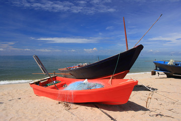 Red Small fishing boats on the beach.
