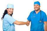 Laughing doctors shaking hands