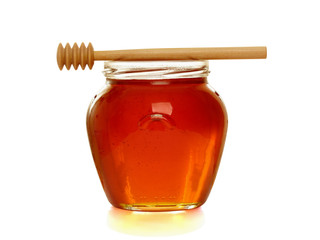 Wooden dipper with jar of honey.