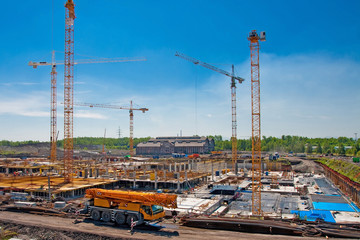 Construcion site with several yellow cranes