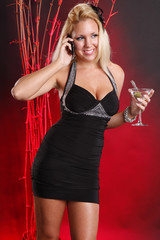 Cute blond in cocktail dress makes a call while having a martini
