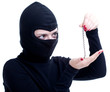 female thief in black balaclava keeping bracelet