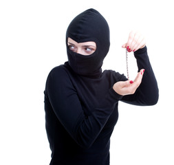 female thief in black balaclava keeping bracelet