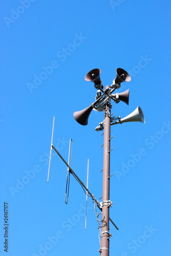 A public address system speakers tower against a sky