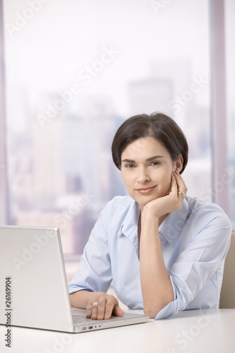 Portrait of female office worker with computer