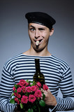 Funny romantic sailor man opening bottle and holding rose flower