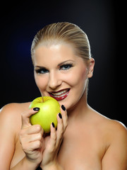 Beautiful woman with bright make-up holding green apple