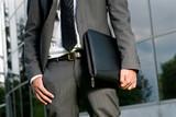 Unrecognizable businessman with suitcase close-up building poster