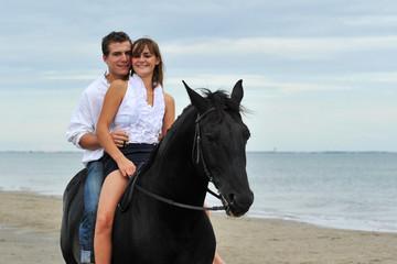 couple a cheval sur la plage
