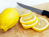 Lemon with slices on cutting board