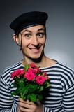Funny romantic sailor man holding rose flowers prepared for a da