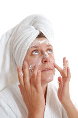 woman putting cream on her face