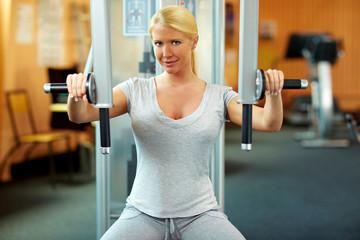 Frau im Fitnesstudio trainiert Muskulatur