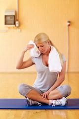 Frau schwitzt im Fitnessstudio