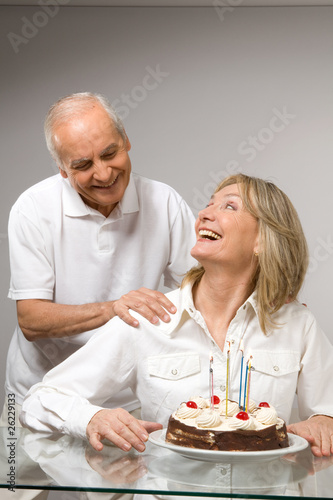 Cheerful couple with a cake