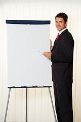 Erfolgreicher Geschäftsmann mit Flipchart bei Präsentation