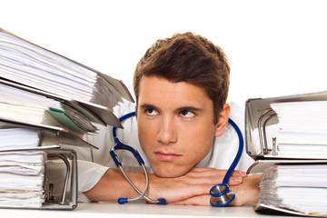 Arzt im Stress mit Akten Stapel. Bürokratie im Krankenhaus.
