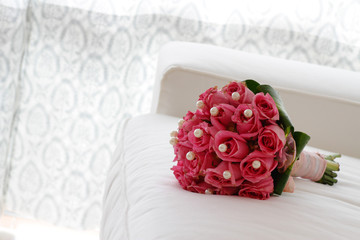A bouquet of pink roses on a white sofa