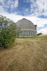 A nice round barn sits partly behind a green bush.