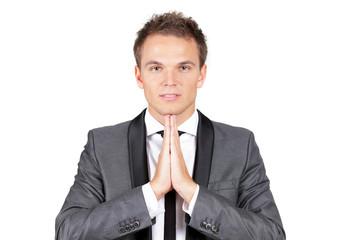 A trendy caucasian businessman making a prayer